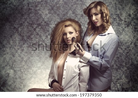 very sexy models posing with open shirt, naked legs and creative hair-style applying bush with brush and looking in camera with sensual eyes. Erotic fashion shoot  - stock photo