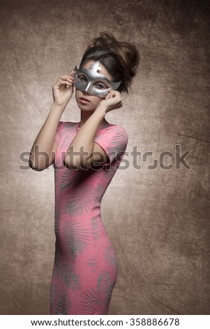 very sexy young woman with brunette hair-style, sexy pink dress and silver mask on her face  - stock photo