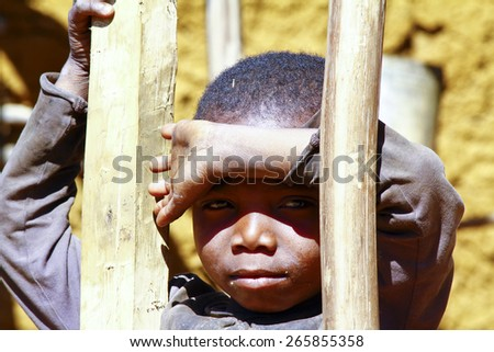Very shy african boy with shadow on his face, poverty in Madagascar