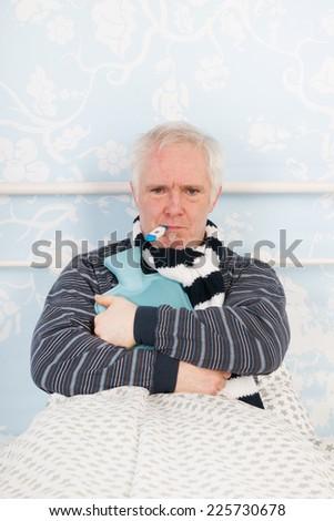 Very sick senior man sitting in bed - stock photo