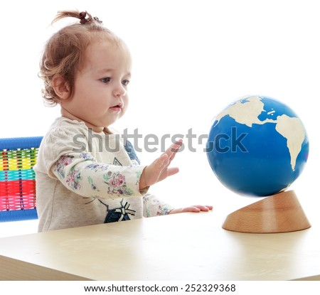 very small but serious little girl spinning globe hand.Isolated on white background, Lotus Children's Center. - stock photo