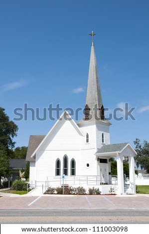 Very small rural christian church with a steeple - stock photo