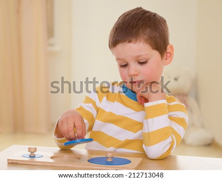 Very smart little boy engaged designer sitting at a table.The concept of development of the child younger years. - stock photo