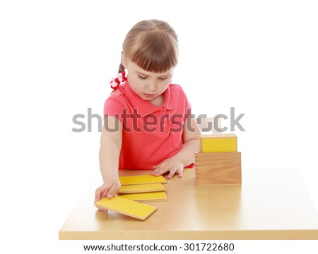 Very smart little girl sitting at a table in a Montessori kindergarten. Girl exploring Montessori material wooden colored rectangular shapes . She lays out in order on the table-Isolated on white - stock photo