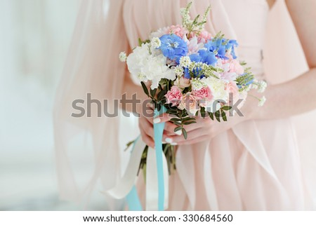 Very soft pink and blue brides bouquet on a background of pink wedding dress in the hands of bride, close-up - stock photo