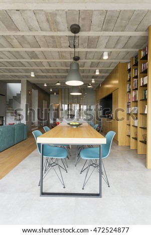 Very spacious dining room joined with living room in post industrial style, with concrete ceiling