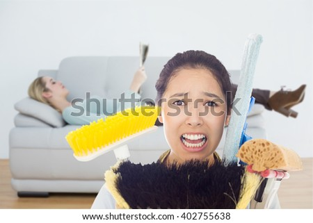 Very stressed woman with cleaning tools against attractive blonde woman reading newspaper lying on couch - stock photo