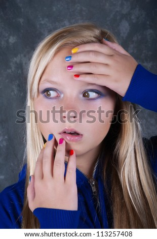 Very surprised beautiful  girl with hands which has colored nails - stock photo