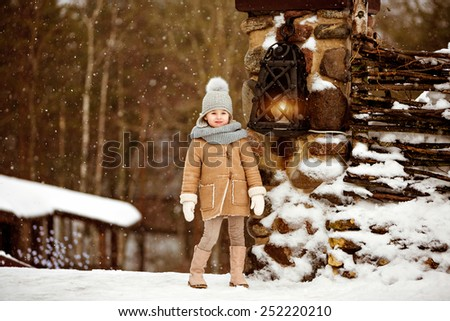 Very sweet beautiful little girl child in a beige coat stands and sad on the background of the winter village near the lantern - stock photo