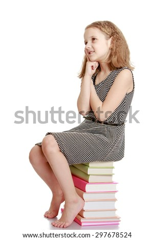 Very sweet, charming, light-haired teenage girl in a light gray silk dress sitting on a stack of books-Isolated on white background - stock photo