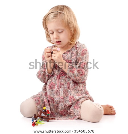 Very thoughtful girl playing with small toys - stock photo