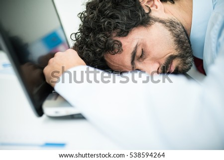 Very tired businessman sleeping on his computer
