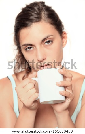 very tired looking woman early in the morning drinking a cup of coffee - selective focus on white cup with copy space - isolated on white