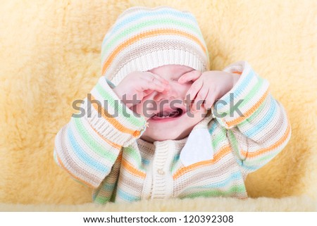 Very tired sleepy baby sitting in a warm sheepskin stroller foot muff - stock photo