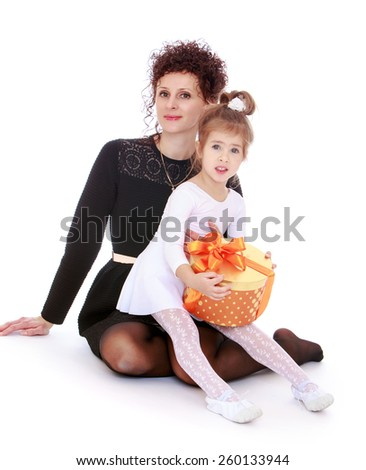 very young and very beautiful mother and daughter with a gift - isolated on white. - stock photo