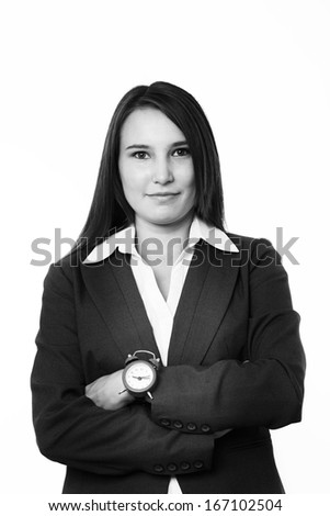 very young happy looking woman in a business suit wearing a traditional alarm clock on her wrist - stock photo