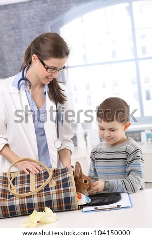 Vet and kid taking rabbit out of carrier at pets' clinic for examination. - stock photo
