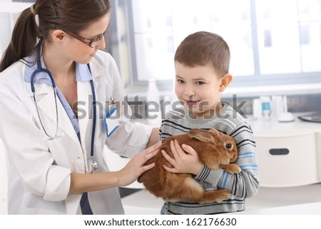 Vet helping little kid holding cute pet rabbit at pets' clinic. - stock photo