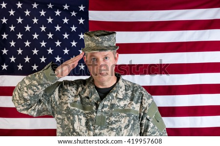 Veteran male soldier, facing forward, saluting with USA flag in background.