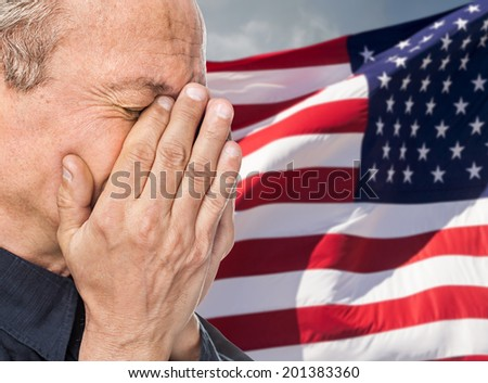 Veteran. Portrait of an elderly man with face closed by hand on USA flag background - stock photo