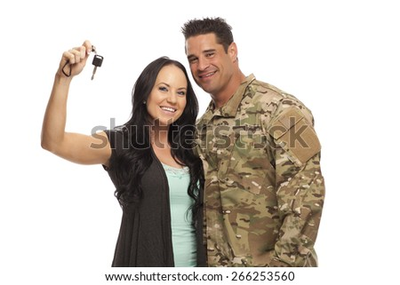 Veteran Soldier buying a car | Happy soldier with his wife holding car key against white background - stock photo
