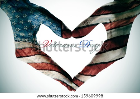 veterans day written in the blank space of a heart sign made with the hands patterned with the colors and the stars of the United States flag - stock photo