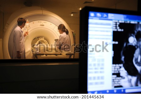 veterinarian doctor working in MRI scanner room with moniter foreground - stock photo