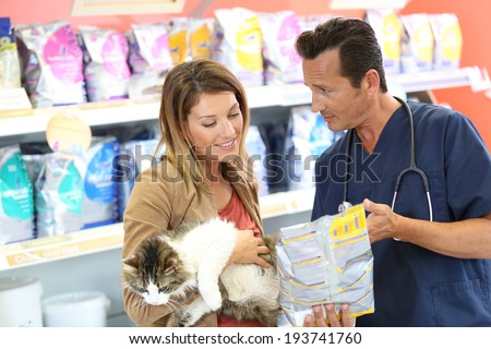 Veterinarian showing pet food to client - stock photo