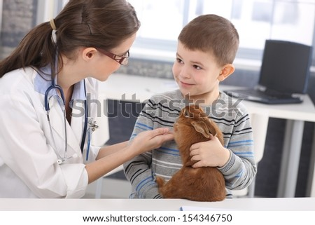 Veterinary and cute kid discussing rabbit treatment at pets' clinic. - stock photo