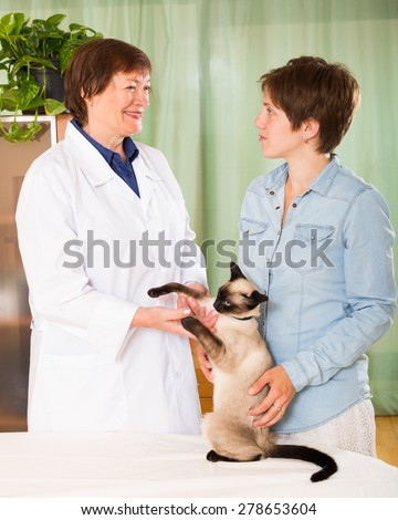 veterinary attendant giving lecture to female cat owner  at veterinary clinic
