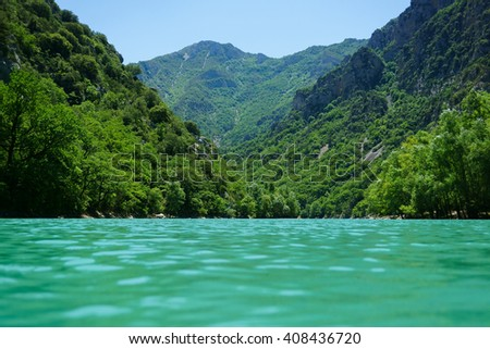 Vew of the low level of turquoise waters of the river on the green landscape of the coast covered with dense vegetation of deciduous trees and pine trees stretching out into the blue haze of the river - stock photo