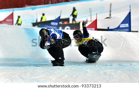 VEYSONNAZ, SWITZERLAND - JANUARY 22: Nate Holland (USA) beats Markus Schairer (GER) in the final of the FIS World Championship Snowboard Cross finals : January 22, 2012 in Veysonnaz Switzerland - stock photo
