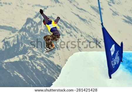 VEYSONNAZ, SWITZERLAND - MARCH 14: Faye GULINI (USA)  taking a high jump in the finals of the Snowboard Cross World Cup: March 14, 2015 in Veysonnaz, Switzerland - stock photo