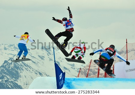 VEYSONNAZ, SWITZERLAND - MARCH 14: Finalists making a high jump competing in the finals of the Snowboard Cross World Cup: March 14, 2015 in Veysonnaz, Switzerland - stock photo