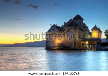 VEYTAUX, SWITZERLAND - JULY 27: Chateau de Chillon, Switzerland at sunset time reflecting in the waters of Lake Geneva (Leman) on the evening of July 27, 2009. The castle dates from the 12th century. - stock photo
