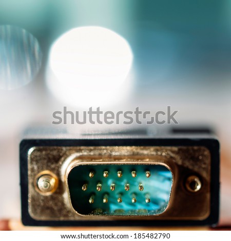 VGA PC input cable connector on de-focused turquoise background - tilt-shift lens used to accent the connection pins and to emphasize the attention on them - stock photo