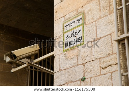 Via dolorosa (Way of Suffer) in Jerusalem Old City, security camera next to street sign - stock photo