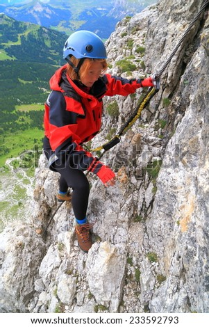 "Via ferrata ""Meisules"" with climber woman on steep rock wall, Sella massif, Dolomite Alps, Italy"