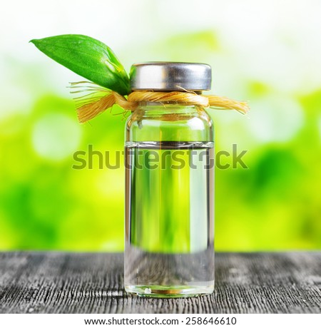 Vial of liquid on a black wooden table and on nature background. Aromatherapy and natural herbal medicine. Essential oils, effective skin care products, face and body products, spa treatments. - stock photo