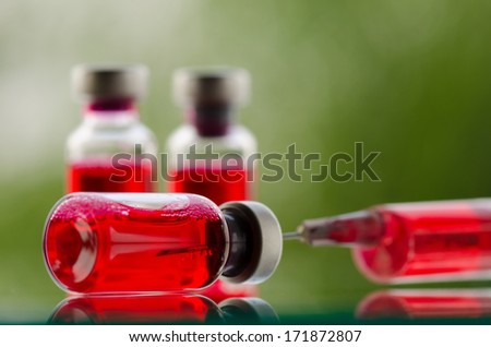 Vials and syringe on glass surface