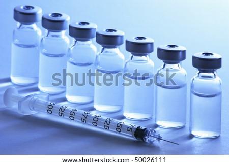 Vials and syringe, tugsten light - stock photo