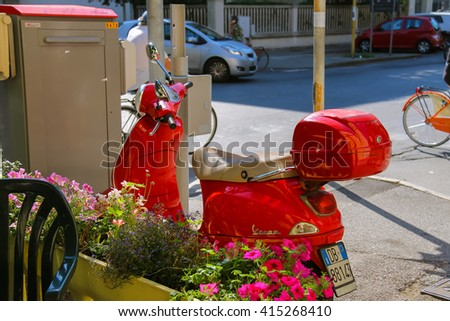 Viareggio, Italy - June 28, 2015: Red moped parking near decorative box with flowers. Province Lucca, Tuscany region of Italy