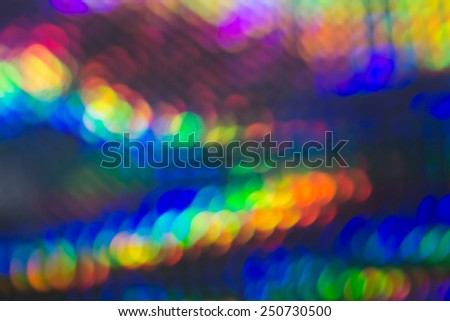 Vibrant abstract background with bokeh and motion blur in the colors of the rainbow with two converging lines of muticolored light for a festive design - stock photo