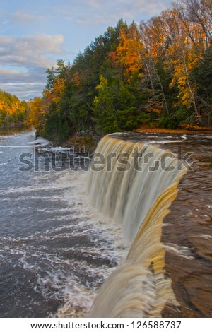 Vibrant autumn landscape with waterfall, vertical