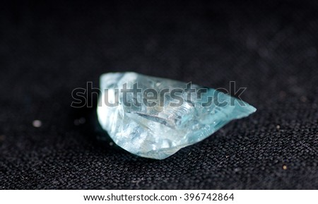 vibrant blue clrea beryl crystal mineral sample on black background - stock photo