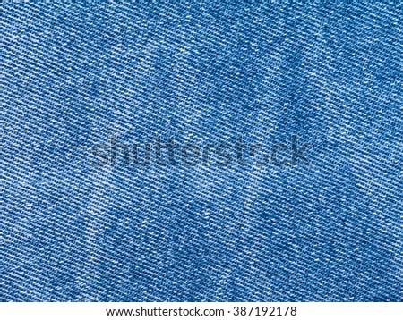Vibrant blue faded jeans denim textile closeup background - stock photo
