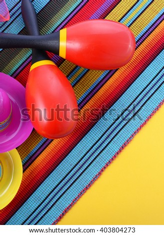 Vibrant Cinco de Mayo background with sombrero hats and maracas on bright festive background, vertical.