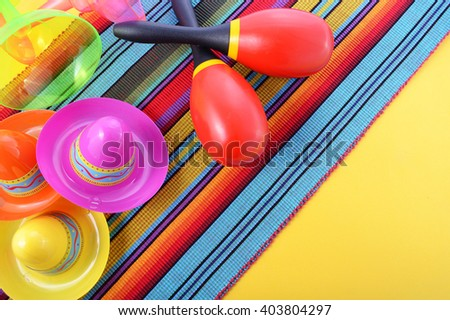 Vibrant Cinco de Mayo background with sombrero hats and maracas on bright festive background.