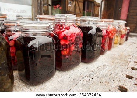 Vibrant clored and testefuly looking compote and jam jars on the table - stock photo