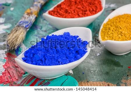 Vibrant color pigments in porcelain bowls on a wooden palette - stock photo